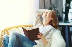 Jovem mulher feliz que lê um livro pela janela imagens de stock