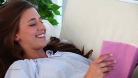 Jovem mulher feliz que lê uma novela video estoque
