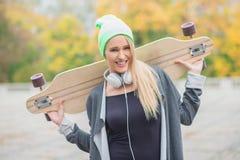 Jovem mulher feliz que leva uma placa do patim Foto de Stock Royalty Free