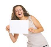 Jovem mulher feliz que mostra a folha do papel vazio Fotos de Stock