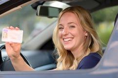 Jovem mulher feliz que mostra fora sua licença de motoristas imagens de stock royalty free