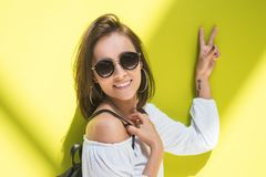 Jovem mulher feliz que mostra o sinal de paz - dois dedos fotografia de stock