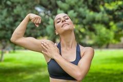 Jovem mulher feliz que mostra seu bíceps imagens de stock royalty free