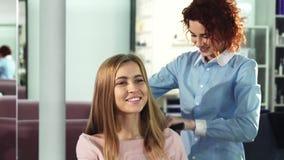 Jovem mulher feliz que obtém lhe o cabelo penteado pelo cabeleireiro profissional no salão de beleza imagem de stock royalty free