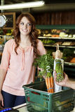 Jovem mulher feliz que olha ausente quando mão que guardara vegetal no supermercado Foto de Stock Royalty Free