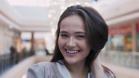 Jovem mulher feliz que olha a câmera com sorriso na alameda Retrato bonito da morena modelo Imagens de Stock Royalty Free