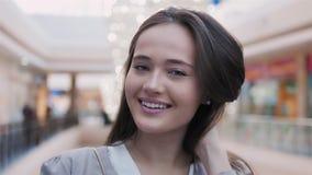 Jovem mulher feliz que olha a câmera com sorriso na alameda Retrato bonito da morena modelo Foto de Stock Royalty Free