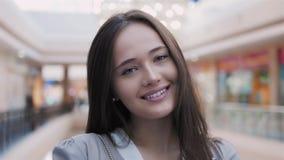 Jovem mulher feliz que olha a câmera com sorriso na alameda Retrato bonito da morena modelo Fotografia de Stock Royalty Free