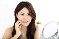 Jovem mulher feliz que olha no espelho Fotografia de Stock Royalty Free