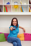 Jovem mulher feliz que olha a tevê Foto de Stock Royalty Free