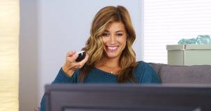 Jovem mulher feliz que olha a tevê no sofá Fotografia de Stock Royalty Free
