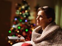 Jovem mulher feliz que olha a tevê na frente da árvore de Natal Fotografia de Stock Royalty Free