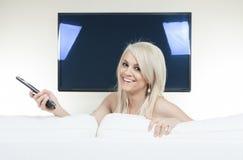 Jovem mulher feliz que olha a tevê no sofá Imagem de Stock