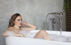 Jovem mulher feliz que relaxa na banheira fotos de stock royalty free