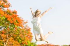 Jovem mulher feliz que salta no parque com seus braços acima no ar fotos de stock royalty free