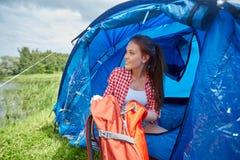 Jovem mulher feliz que senta-se na barraca no acampamento Foto de Stock Royalty Free