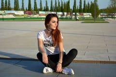 Jovem mulher feliz que senta-se na terra na rua e que olha o sol imagem de stock