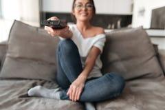 Jovem mulher feliz que senta-se na tevê do relógio do sofá em casa imagem de stock