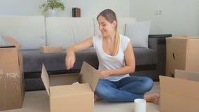 Jovem mulher feliz que senta-se no assoalho e que desembala caixas de cartão com coisas video estoque