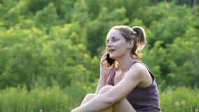 Jovem mulher feliz que senta-se no gramado verde e que fala no telefone ou no smartphone video estoque