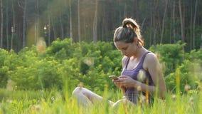 Jovem mulher feliz que senta-se no smartphone verde do gramado e dos usos no campo cênico no fundo do por do sol filme