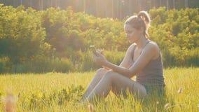 Jovem mulher feliz que senta-se no smartphone verde do gramado e dos usos no campo cênico no fundo do por do sol video estoque