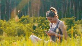Jovem mulher feliz que senta-se no smartphone verde do gramado e dos usos no campo cênico no fundo do por do sol vídeos de arquivo