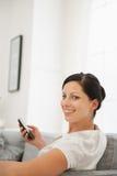 Mulher feliz que senta-se no sofá e que guardara o móbil Imagem de Stock Royalty Free