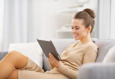 Jovem mulher feliz que senta-se no sofá e que trabalha no PC da tabuleta