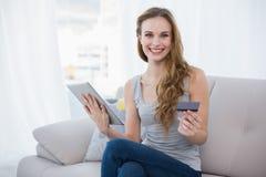Jovem mulher feliz que senta-se no sofá usando a tabuleta para comprar em linha Fotografia de Stock