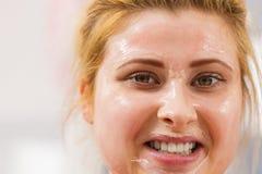 Jovem mulher feliz que tem a máscara do gel na cara imagens de stock