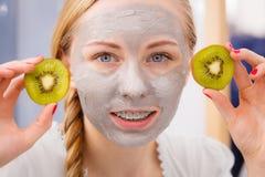 Jovem mulher feliz que tem a máscara protetora que guarda o quivi imagens de stock royalty free