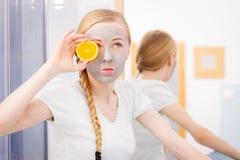 Jovem mulher feliz que tem a máscara protetora que guarda o quivi foto de stock royalty free