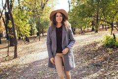 Jovem mulher feliz que tem o tempo do divertimento no outono fora Corredor de salto de sorriso feliz da menina na floresta foto de stock royalty free