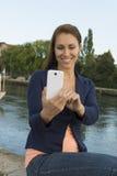 Jovem mulher feliz que toma imagens com telefone esperto Foto de Stock Royalty Free