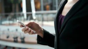 Jovem mulher feliz que usa o telefone esperto no shopping Freelancer da mulher de negócios com o smartphone no terminal de aeropo Imagem de Stock Royalty Free