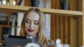 Jovem mulher feliz que usa a tabuleta com sorriso no café filme