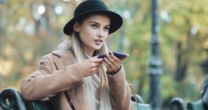 Jovem mulher feliz que usa uma função do reconhecimento de voz do smartphone Ela que senta-se no banco no parque e nas ordens do  imagem de stock