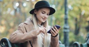 Jovem mulher feliz que usa uma função do reconhecimento de voz do smartphone Ela que senta-se no banco no parque e nas ordens do  video estoque