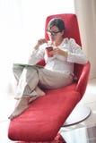 A jovem mulher feliz relaxa em casa no sofá Foto de Stock Royalty Free