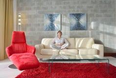 A jovem mulher feliz relaxa em casa no sofá Imagens de Stock Royalty Free