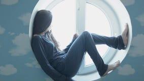 A jovem mulher feliz relaxa em uma janela redonda Uma menina bonita de sorriso em uma janela em uma sala azul Papéis de parede co vídeos de arquivo