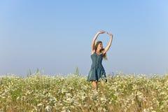 A jovem mulher feliz salta no campo dos camomiles Imagem de Stock