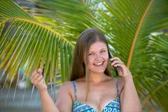 Jovem mulher feliz sob a palmeira que fala no telefone esperto fotografia de stock