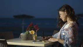 A jovem mulher feliz termina escrever memórias românticas no diário, relaxa no beira-mar filme