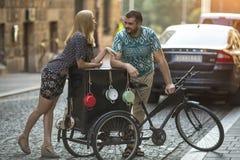 A jovem mulher flerta com um homem perto da bicicleta do vintage na rua Foto de Stock