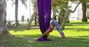 Jovem mulher flexível que faz esticando exercícios filme