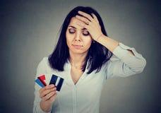Jovem mulher forçada no débito que guarda cartões de crédito múltiplos imagens de stock royalty free