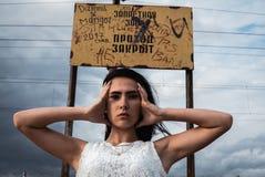 Jovem mulher forçada pensativa guarda sua cabeça em suas mãos fotos de stock