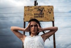 Jovem mulher forçada pensativa guarda sua cabeça em suas mãos foto de stock royalty free
